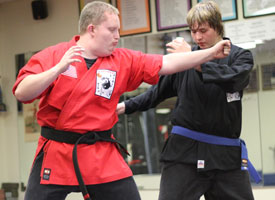 instructor allen teaches repeating fist technique for a green belt